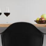 Servizio fotografico di hotel. Dettaglio di scrivania di un hotel trentino a Rovereto, seggiola davanti a un piano in legno con due bicchieri di vino rosso a sinistra e cesto di mele a destra, il piano in legno e all'altezza degli occhi.