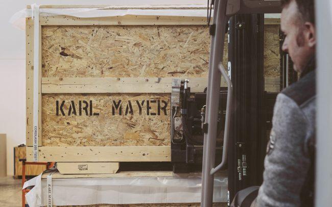 muletto carica una cassa dove c'è scritto il nome dell'azienda. Immagine scattata per evento aziendale in Trentino