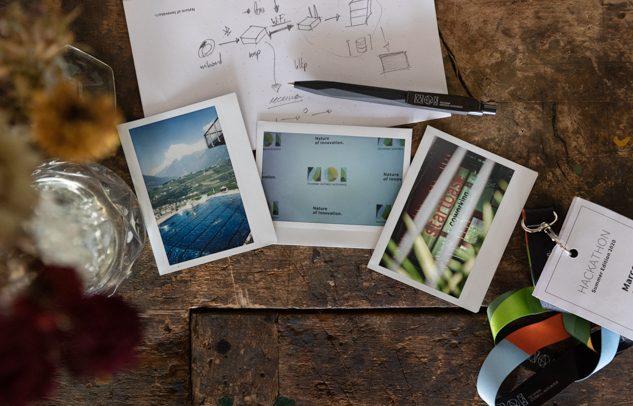 evento NOI Techpark Summer edition. Dettaglio di un tavolo con polaroid e foglio di carta. Startbase di Lido Schenna, Merano.